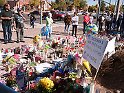 """15 JANUARY 2010 - TUCSON, AZ:   A woman writes a note for Congresswoman Gabrielle Giffords in front of a memorial at Giffords' office in Tucson, AZ, Saturday, January 15. Six people were killed and 14 injured in the shooting spree at a """"Congress on Your Corner"""" event hosted by Arizona Congresswoman Gabrielle Giffords at a Safeway grocery store in north Tucson on January 8. Congresswoman Giffords, the intended target of the attack, was shot in the head and seriously injured in the attack but is recovering. Doctors announced that they removed her breathing tube Saturday, one week after the attack. The alleged gunman, Jared Lee Loughner, was wrestled to the ground by bystanders when he stopped shooting to reload the Glock 19 semi-automatic pistol. Loughner is currently in federal custody at a medium security prison near Phoenix.  PHOTO BY JACK KURTZ"""