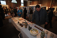 """Pater Cleary looks at pottery during the Yoknapatawpha Arts Council's """"Art For Everyone"""" fundraiser in Oxford, Miss. on Tuesday, October 18, 2011."""