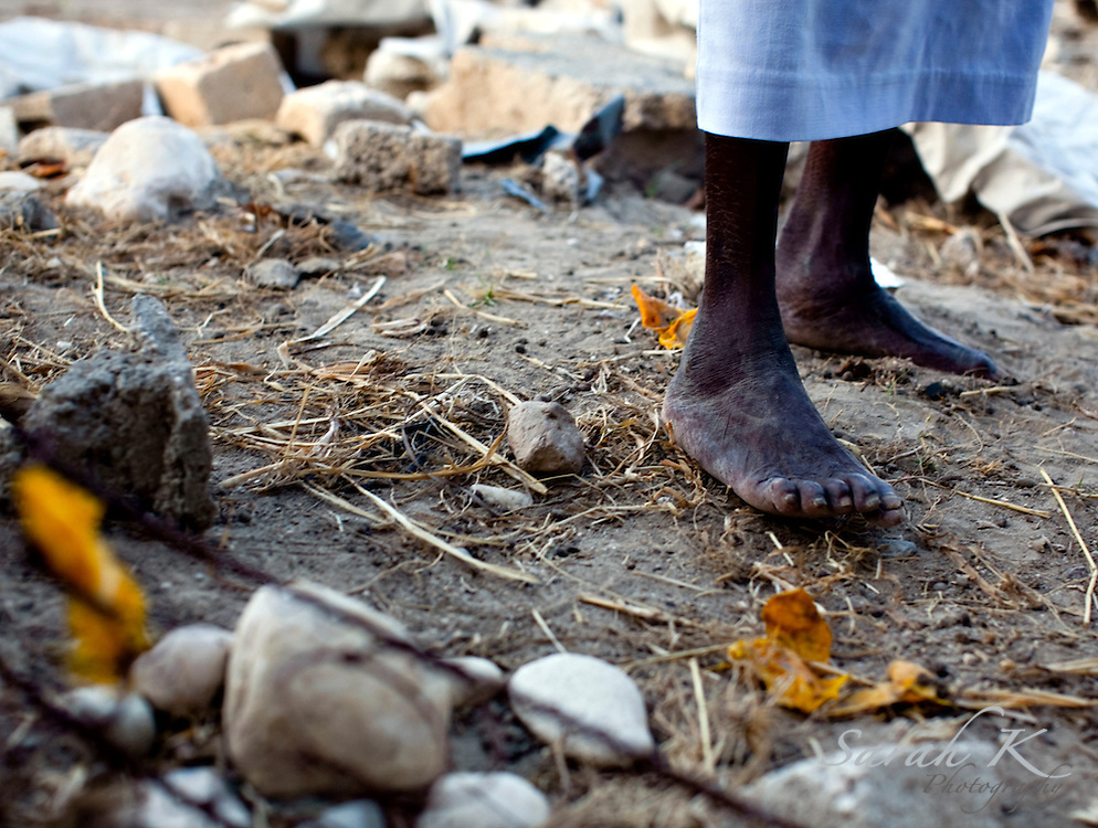 "Lea Beauplau, 63, single mother of six, stands on what's left of her home in Gonaives after the floods.  She lost everything she owned in the flood, and she lost her father. ""Things can be replaced,"" she said. ""But you can't bring back my father."" Today, Beauplau lives in a small room in her neighbor's home, along with her six children and five other flood survivors."