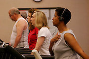 Every week, the Revis family (foreground, Rosemary on treadmill listening to music) faithfully trekked to the health club in the Wakefield Medical Center, a hospital complex in Raleigh, North Carolina, for two-hour exercise sessions. They enjoyed the workouts, but found them so time-consuming that they wound up eating more fast food than ever. Fearing its potential impact on their health, they ultimately gave up the club in favor of dining and exercising at home. (Supporting image from the project Hungry Planet: What the World Eats.)
