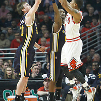 10 March 2012: Chicago Bulls point guard Derrick Rose (1) takes a jumpshot over Utah Jazz shooting guard Gordon Hayward (20) and Utah Jazz small forward Josh Howard (8) during the Chicago Bulls 111-97 victory over the Utah Jazz at the United Center, Chicago, Illinois, USA.