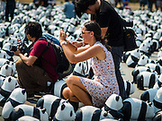 "04 MARCH 2016 - BANGKOK, THAILAND: A tourist and Thai press photographers take pictures of the ""1600 Pandas+ World Tour in Thailand: For the World We Live In and the Ones We Love"" exhibit on Sanam Luang in Bangkok. The 1600 paper maché pandas, an art installation by French artist Paulo Grangeon will travel across Bangkok and parts of central Thailand for the next week and then will be displayed at Central Embassy, a Bangkok shopping mall, until April 10. The display of pandas in Thailand is benefitting World Wide Fund for Nature - Thailand and is sponsored by Central Embassy with assistance from the Tourism Authority of Thailand and Bangkok Metropolitan Administration and curated by AllRightsReserved Ltd.     PHOTO BY JACK KURTZ"