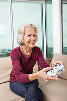 Happy senior woman playing video game on sofa at home