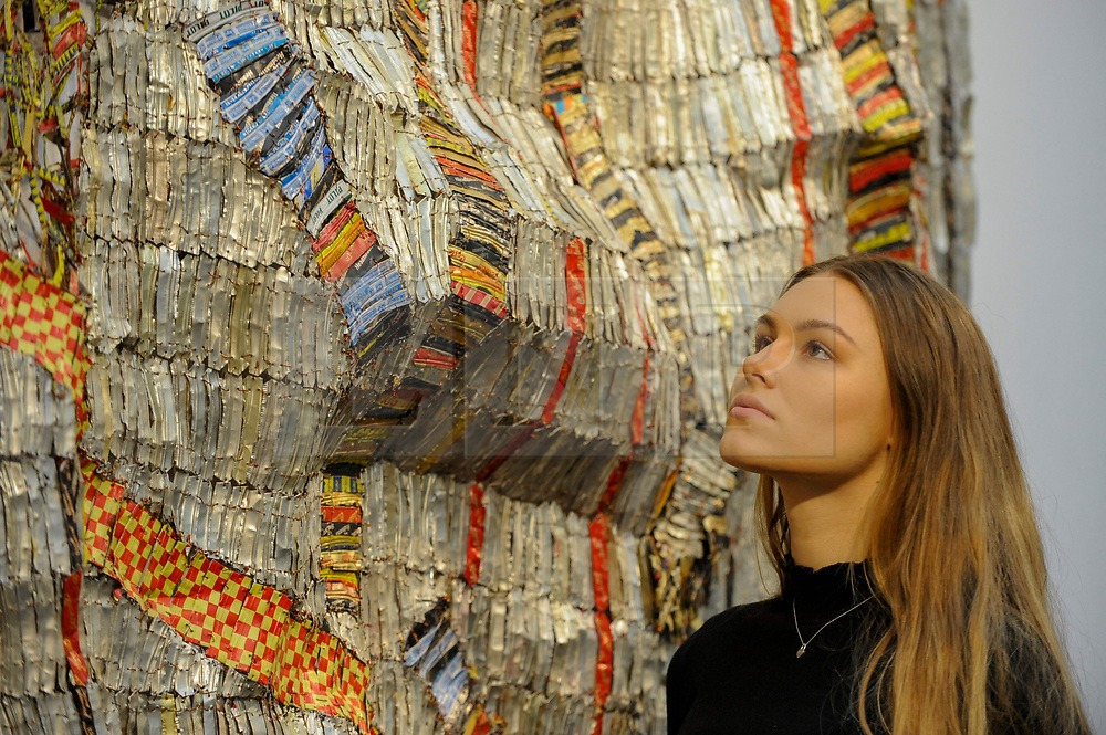 """© Licensed to London News Pictures. 12/05/2017. London, UK.   A staff member views (C) """"Earth Developing More Roots"""", 2011, by El Anatsui (Ghana) (Est. GBP 650-850k) at the preview for the first sale dedicated to Modern and Contemporary African Art at Sotheby's New Bond Street.  The sale features over 115 artworks by over 60 different artists from 14 countries across the continent. Photo credit : Stephen Chung/LNP"""