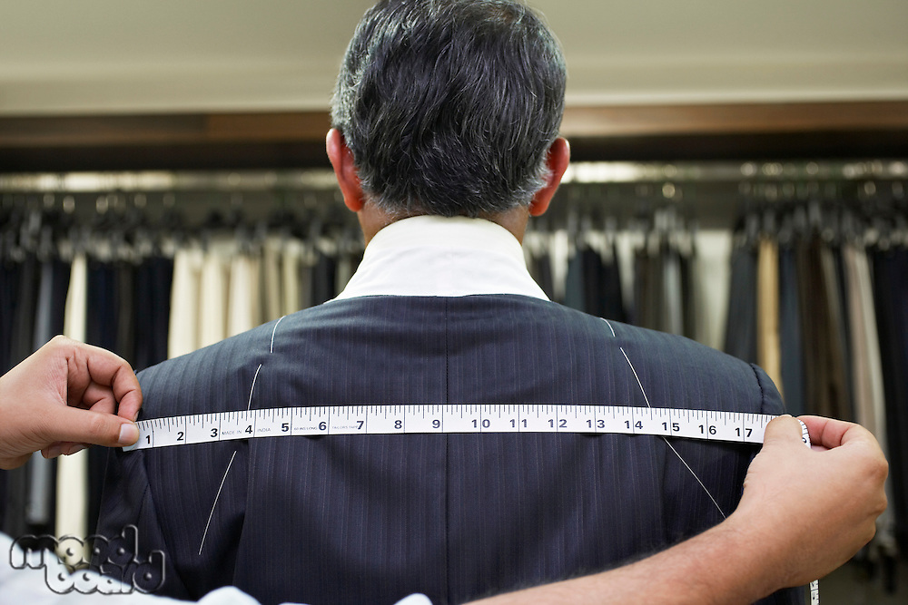 Tailor measuring business man for suit close up