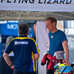 July 6, 2012 - Flying Lizard Motorsport Porsche driver Jörg Bergmeister chats with a Michelin engineer in the paddock during the American Le Mans Northeast Grand Prix weekend at Lime Rock Park in Lakeville, Conn.
