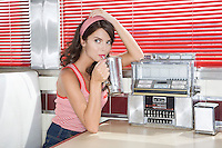Young Woman Drinking a Milkshake in a Diner
