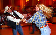 "09 DECEMBER 2002 - LAS VEGAS, NEVADA, USA: Justin Bond, from Colorado Springs, CO, dances with Crystal Sloyer, from Lake Forest, CA, in a bar at the Gold Coast Casino, Dec. 9, 2002, during the National Finals Rodeo. The NFR is the ""Super Bowl"" rodeo; hundreds of thousands of rodeo fans come to Las Vegas for 10 days every December to participate, in one way or another, in the NFR. The Gold Coast hosts a number of NFR related events, including trophy presentations and free dances, during the NFR and many spectators and contestants come to the Gold Coast to watch television feeds of the rodeo and gamble. PHOTO BY JACK KURTZ"