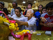 14 JANUARY 2016 - CHACHOENGSAO, CHACHOENGSAO, THAILAND: A Buddhist nun (also called Bhikkhuni) makes merit among the statues of the Buddha at Wat Sothon. Wat Sothon, in Chachoengsao, is one of the largest Buddhist temples in Thailand. Thousands of people come to the temple every day to pray for good luck, they make merit by donating cooked eggs and cash to the temple. The temple dates from the Ayutthaya period (circa 18th century CE).         PHOTO BY JACK KURTZ