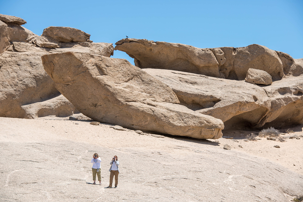 Tourists photographing the sights next to a large boulder formation in the Namib desert, located in Namibia, Africa.