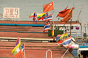 21 APRIL 2014 - CHIANG SAEN, CHIANG RAI, THAILAND: Chinese flags flying over Chinese river boats tied up in the port in Chiang Saen, Thailand. Chiang Rai province in northern Thailand is facing a drought this year. The 2014 drought has been brought on by lower than normal dry season rains. At the same time, closing dams in Yunnan province of China has caused the level of the Mekong River to drop suddenly exposing rocks and sandbars in the normally navigable Mekong River. Changes in the Mekong's levels means commercial shipping can't progress past Chiang Saen. Dozens of ships are tied up in the port area along the city's waterfront.      PHOTO BY JACK KURTZ
