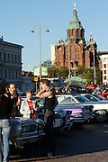 During summer from June to Septemper, every first Friday of the month is Vintage Car Cruising Night. Hundreds of classic American cars cruise around downtown Helsinki and meet at special places to have a good time, here at Kauppatori (Market Square), Uspenski orthodox cathedral in background. Rockabillies having a chat and a beer.