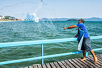 Homem escando com rede de pesca no trapiche da Praia de Canasvieiras. Florianópolis, Santa Catarina, Brazil. / Man fishing with a fishing net on the pier of Canasvieiras Beach. Florianopolis, Santa Catarina, Brazil.