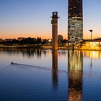 Canoeist on the Guadalquivir river in front of Schindler and Sevilla towers, Seville, Spain.
