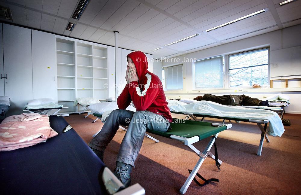 Nederland, Amsterdam , 8 december 2012..Een dakloze ontwaakt in 1 van de geimproviseerde slaapzalen van het voormalige kantorenpand aan de Laan van Vlaanderen, dat tijdelijk dienst doet  als daklozenopvang vanwege de vrieskou...Verwacht wordt dat dit weekend zo'n 220 daklozen zich zullen aanmelden om hier te overnachten. .Foto:Jean-Pierre Jans