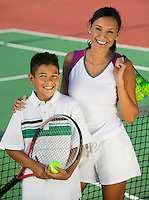 Mother and son by net on tennis court portrait high angle view