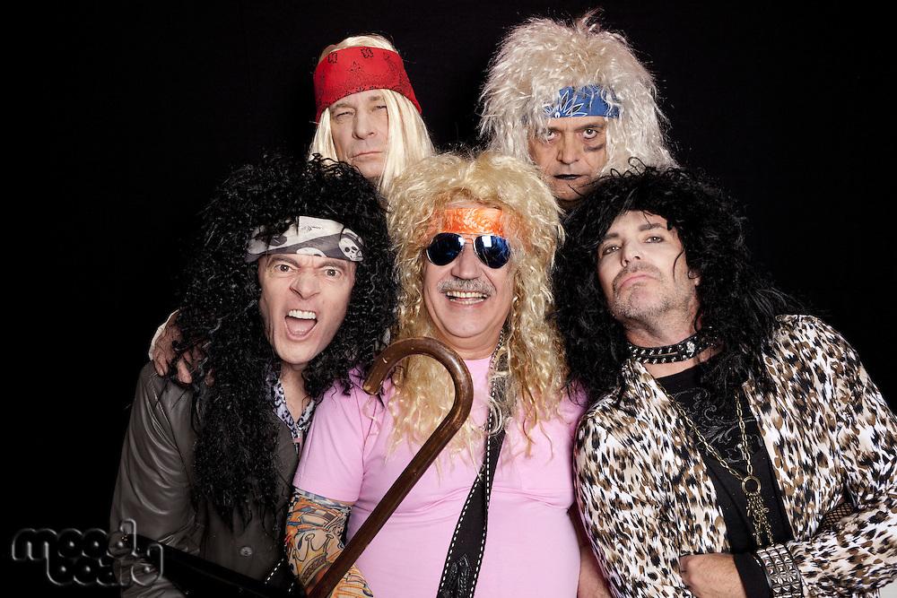 Portrait of rock musicians making funny faces over black background