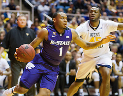 Feb 11, 2017; Morgantown, WV, USA; Kansas State Wildcats guard Carlbe Ervin II (1) drives past West Virginia Mountaineers forward Elijah Macon (45) during the first half at WVU Coliseum. Mandatory Credit: Ben Queen-USA TODAY Sports