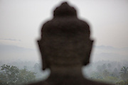 The landscape can be seen over the shoulders of a seated Buddha statue at Borobudur temple in Central Java, Indonesia.