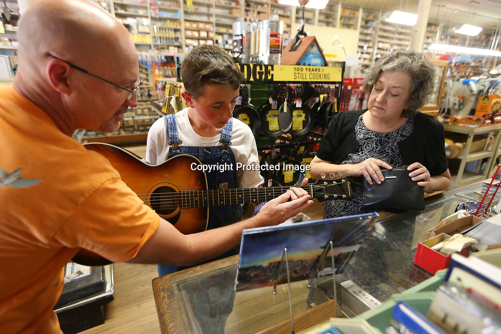 Allan Cayson, as longtime Tupelo Hardware employee, Forrest Bobo, shows Tanner Palmer as a young Elvis Presley, play a cord on the guitar while Jennifer Collins, as Elvis's mother Gladys, watches as they rehearse their reenactment of the day Elvis and his mother walked into Tupelo Hardware and purchased his first guitar. The reenactments will take place on Friday at 1, 2 and 3:00, and Saturday at 11:30 and 12:30 at Tupelo Hardware in Tupelo.