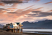 Sunset over the shops and restaurants on Homer Spit along the Kachemak Bay in Homer, Alaska. Homer is known as the End of the Road and is surrounded by wilderness and ocean.