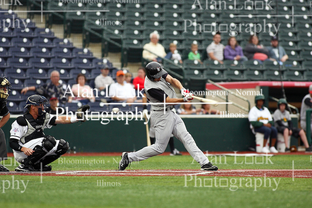 09 June 2011: Scott Houin swings through a pitch as the ball heads for the glove of Jeff Dunbar during a game between the Lake Erie Crushers and the Normal Cornbelters at the Corn Crib in Normal Illinois.