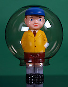 A toy doll encased in a glass globe
