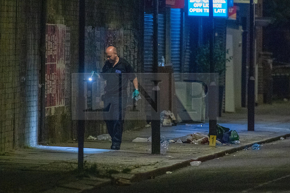 © Licensed to London News Pictures. 26/06/2020. London, UK. A forensic investigator uses a torch to look for evidence around medial kits left by paramedics inside the police cordon. A person has been stabbed on Du Cane Road in East Acton on Thursday 25th June 2020. A cordon closed off a large section of the road underneath a railway bridge where two vehicles remained. Photo credit: Peter Manning/LNP