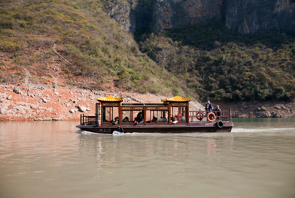 Excursion boat on Goddess Stream, tributary of the Yangtze River, China.  This was once a wild river carving through a rugged canyon, tamed now by the construction of the Three Gorges Dam.