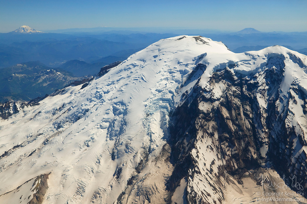 Three of Washington's dominant volcanoes are visible in this aerial view. Mount Rainier is in the foreground. Mount St. Helens is visible in the saddle of Rainier's peak. Mount Adams is in the upper-left corner. Mount Hood in Oregon, which is also part of the Cascade range, is faintly visible on the horizon between Adams and the summit of Rainier.