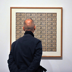 © Licensed to London News Pictures. 07/02/2012, London, UK. A man walks in front of works by Yayoi Kusama featuring banknotes. Press preview of Yayoi Kusama at the Tate Gallery Bankside today 7th February 2012. The exhibition spans six decades of the artists work. Kusama is one of Japan's best known living artists.  Photo credit : Stephen Simpson/LNP