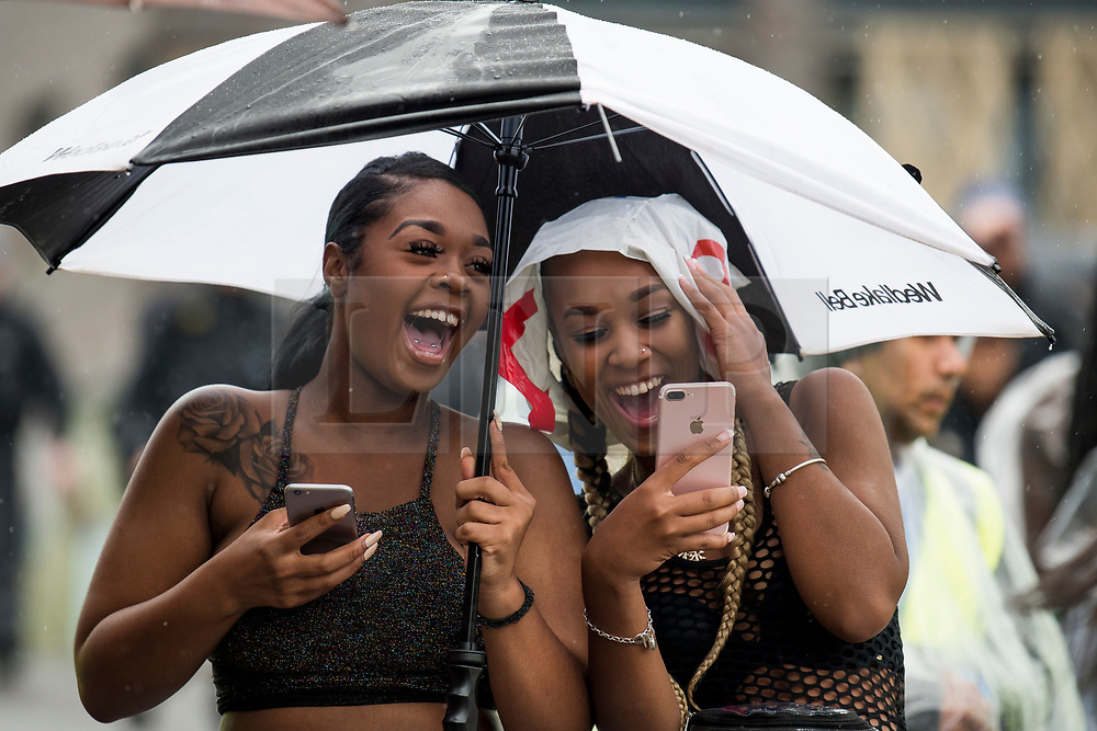 © Licensed to London News Pictures. 26/08/2018. London, UK. Two young carnival goers shelter under an umbrella at family day of the 2018 Notting Hill Carnival. Up to 1 million people are expected to attend this weekend's event that is one of the worlds largest street festivals. Photo credit: Ben Cawthra/LNP