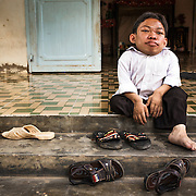 CAPTION: Bui Huong's son, Sang, sitting on the steps outside their house. LOCATION: Long Tuyen, Can Tho, Vietnam. INDIVIDUAL(S) PHOTOGRAPHED: Le Thanh Sang.