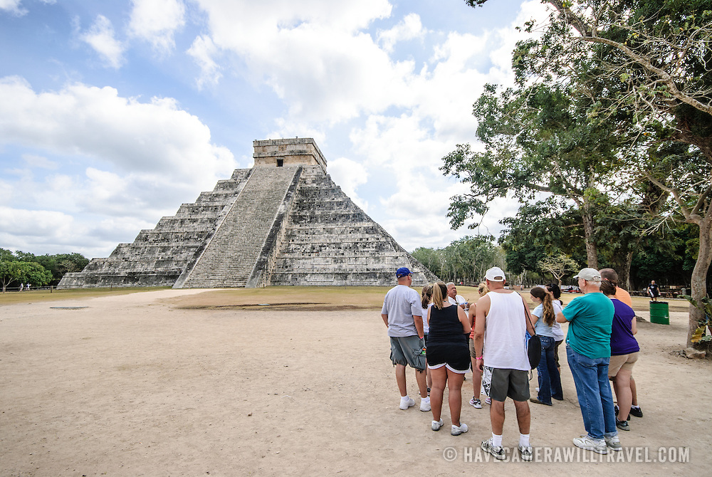 Temple of Kukulkan (El Castillo) at Chichen Itza Archeological Zone, ruins of a major Maya civilization city in the heart of Mexico's Yucatan Peninsula. A group of tourists stands to the right of frame.