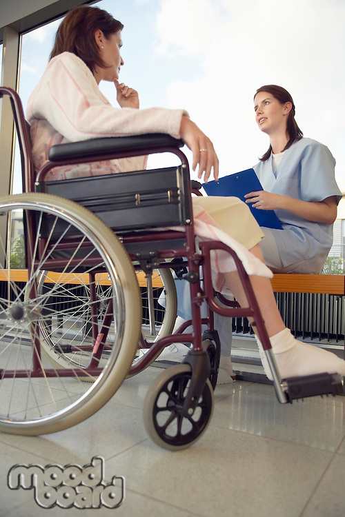 Nurse talking to patient in wheelchair low angle view