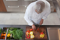 Mid- adult chef dices peppers  overview