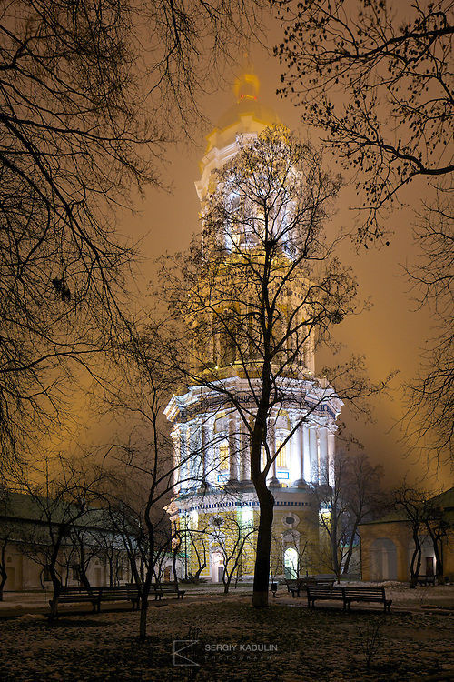 Bell tower of Kyiv-Pechersk Lavra at night. Contrasting trees'  silhouettes create frame around the bell tower highlighted by the beams from both sides in the foggy air. Winter, 2015.