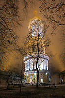 Bell tower of Kyiv-Pechersk Lavra at night. Contrasting trees'  silhouettes create frame around the bell tower highlighted by the beams from both sides in the foggy air. Winter, 2015.<br />