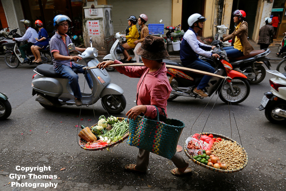 A woman selling fruit and vegetables walks through the Old Quarter in Hanoi, Vietnam