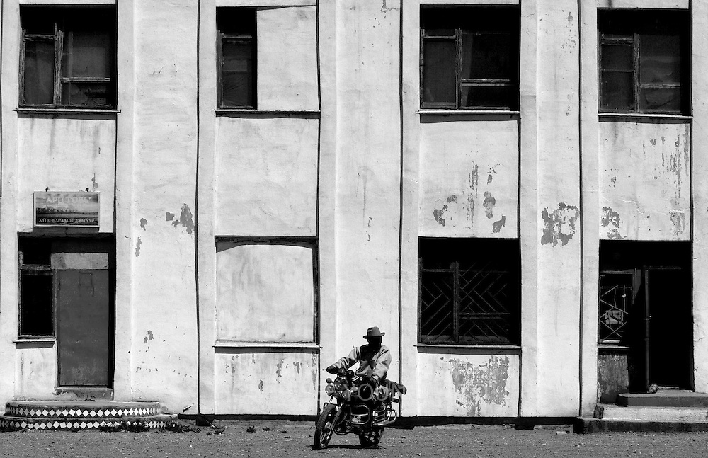 A nomad riding a motorcycle in front of an abandoned building in a town in Mongolia.