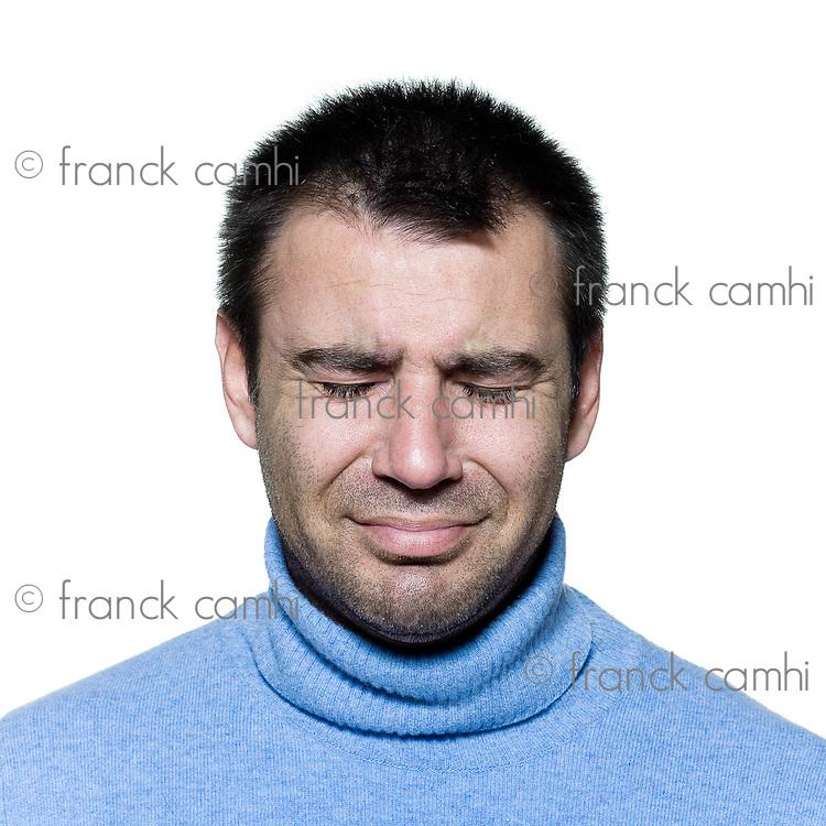 studio portrait on isolated background of a stubble man crying sad depression