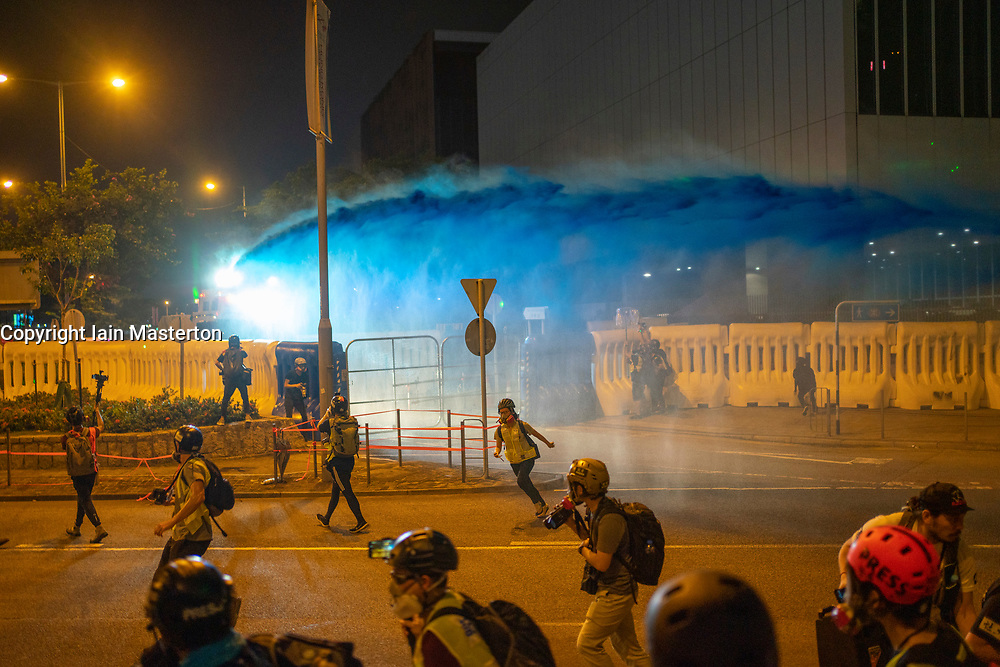 Hong Kong. 28 September 2019. Police fire water cannon at demonstrators outside the Government Headquarters at Tamar in Admiralty district of the city. The water is dyed blue and is laced with a stinging ingredient. Crowds had gathered at Tamar to commemorate 5th anniversary of Umbrella Movement. Small group of protestors provoked police away from the rally. Iain Masterton/Alamy Live News