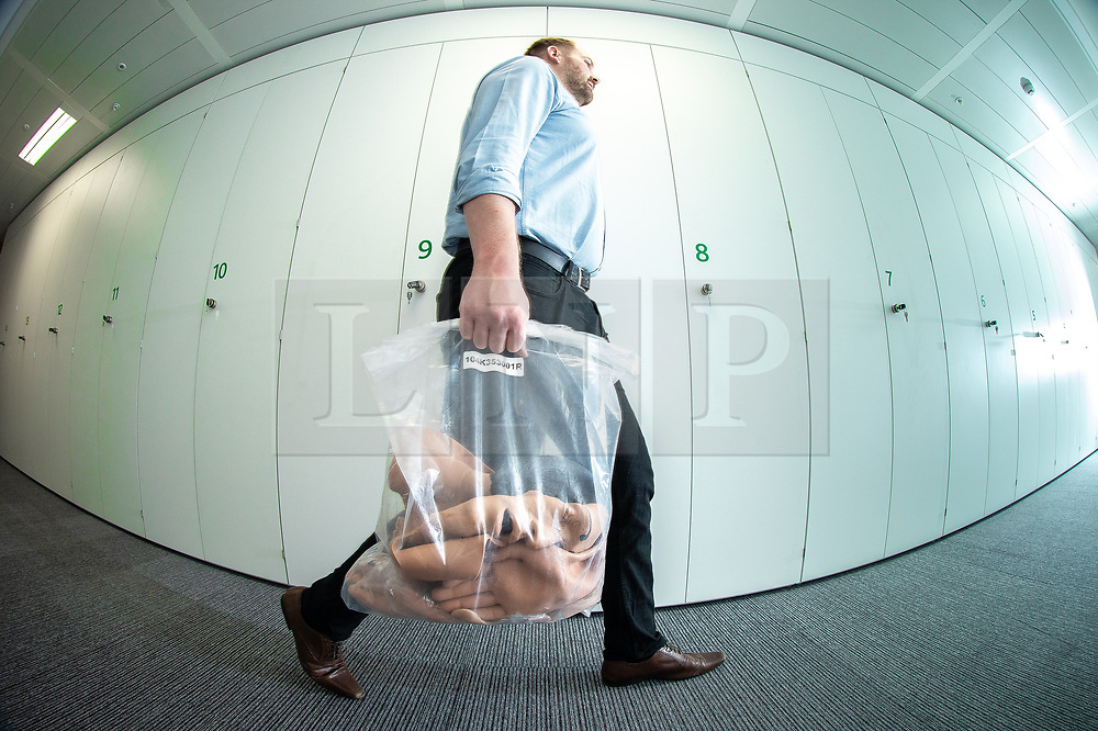© Licensed to London News Pictures. 10/07/2019. Manchester, UK. Lifelike rubber body parts are carried past storage lockers at the new facility. General Medical Council (GMC) staff prepare for the opening of the regulator's new test facility in central Manchester. The £2.5m clinical assessment centre in the city's Spinningfields district will assess the skills of overseas-trained doctors who want to work in the UK. Once it opens in early August, more than 1,000 doctors per month will undergo a series of practical tests to show they have the skills required for a licence to practise medicine in the UK. It will replace the GMC's existing test centre, which has a more limited capacity. Photo credit: Joel Goodman/LNP