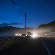 Car lights illuminate the mist gathering at dusk in West Virginia.