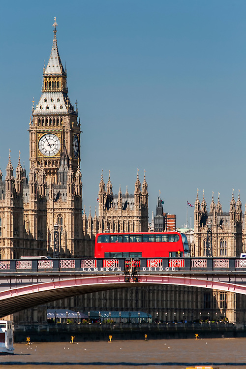 A red London bus passing over Lambeth Bridge with Big Ben in the background
