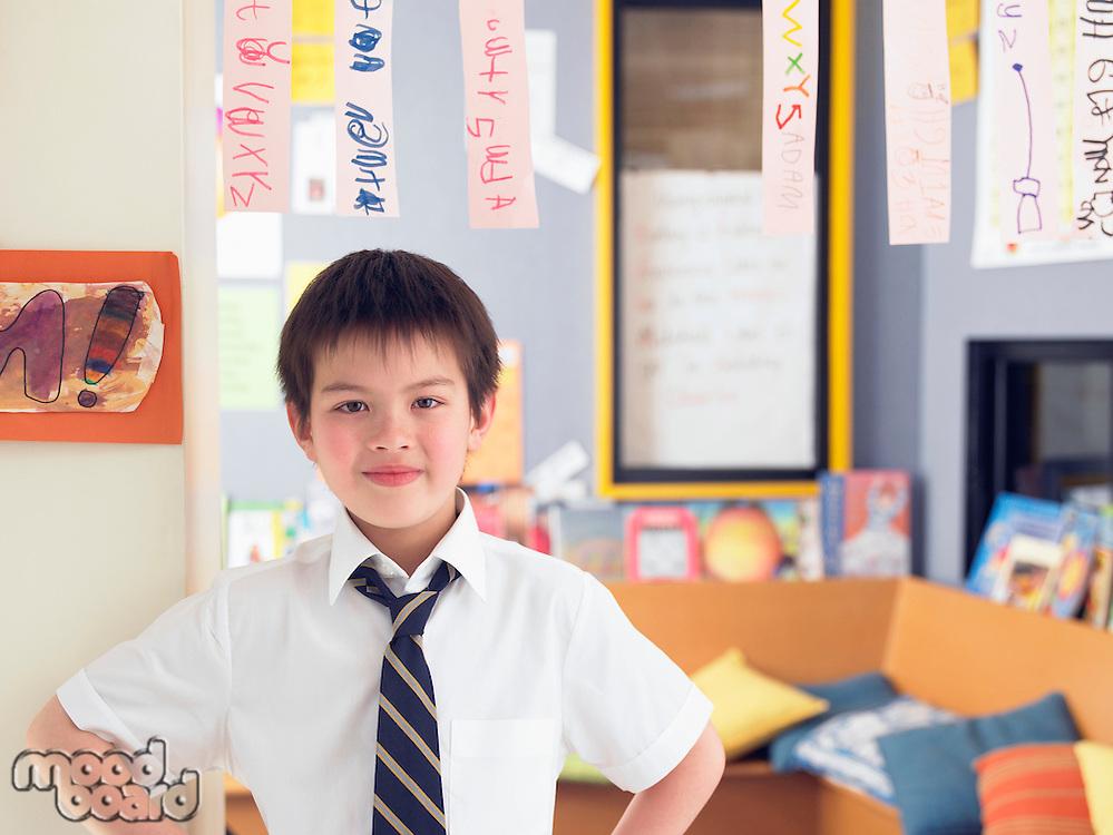 Elementary schoolboy standing in classroom portrait