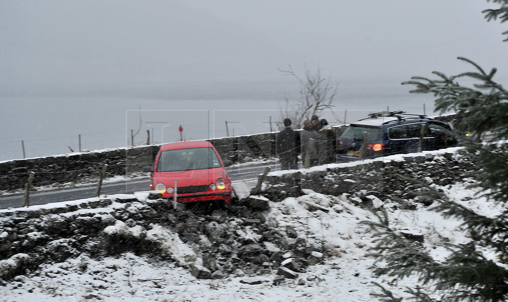 ***UPDATED CAPTION with location ***(c) Licenced to London News Pictures 29/01/2015. Cumbria, UK. A car skids on snow on the A591 near Thirlmere and hits a wall. Snow affects the higher fells in the Lake District. Photo credit : Harry Atkinson/LNP
