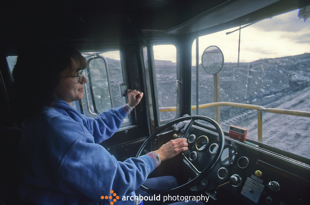 Woman driving large mining truck. Town of Faro. Canada's largest open-pit lead-zinc mine.