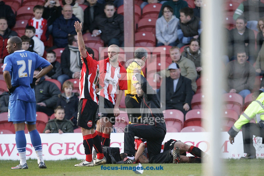 London - Saturday, March 28th, 2009: Brentford physio David Appanah (R) and Sam Wood (2nd L) call for assistance as team mate Charlie MacDonald lies injured during the Coca Cola League Two match at Griffin Park, London. (Pic by Mark Chapman/Focus Images)