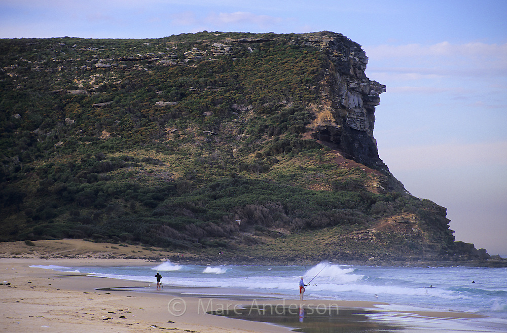 A man fishing on a beach with high cliffs in the background at Garie Beach in the Royal National Park in Australia.